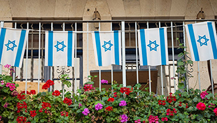 String of Israeli flags on fence with flowers