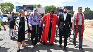 Interfaith leaders holding hands and marching for immigrant justice